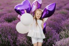 Menina bonito feliz no campo da alfazema com balões roxos Conceito da liberdade fotografia de stock royalty free
