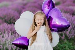 Menina bonito feliz no campo da alfazema com balões roxos Conceito da liberdade fotografia de stock