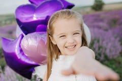 Menina bonito feliz no campo da alfazema com balões roxos Conceito da liberdade imagem de stock