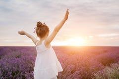 Menina bonito feliz no campo da alfazema no por do sol Conceito da liberdade imagem de stock