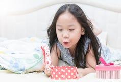 Menina bonito feliz que abre uma caixa de presente do ` s do Valentim Imagens de Stock Royalty Free