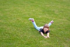 Menina bonito feliz que encontra-se em um gramado Foto de Stock Royalty Free