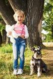 Menina bonito feliz que senta-se no parque com seu cão Imagem de Stock Royalty Free
