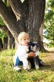 Menina bonito feliz que senta-se no parque com seu cão Imagens de Stock