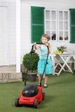 A menina bonito feliz sega o gramado pelo cortador de grama vermelho Imagens de Stock