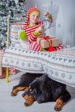 A menina bonito feliz vestiu-se nos pijamas listrados que sentam-se na sala decorada do ano novo em casa Fotografia de Stock