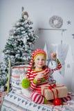 A menina bonito feliz vestiu-se nos pijamas listrados que sentam-se na sala decorada do ano novo em casa Foto de Stock Royalty Free