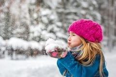A menina bonito funde a neve das mãos Fotografia de Stock