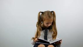 A menina bonito furada abre o livro e olha o livro Menina de primeiro grau que guarda um livro e uma leitura vídeos de arquivo