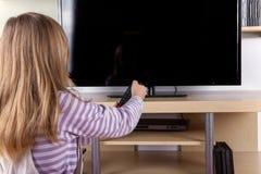 Menina bonito girando de ligar/desligar a televisão com um controlo a distância foto de stock royalty free