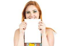 A menina bonito guarda o cartão grande verticalmente Weari Redheaded da menina Imagens de Stock