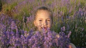 A menina bonito joga arbustos da alfazema na natureza vídeos de arquivo
