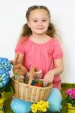 A menina bonito joga com uma cesta dos ovos da páscoa Fotografia de Stock