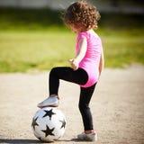 A menina bonito joga o futebol Fotos de Stock Royalty Free