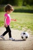 A menina bonito joga o futebol Foto de Stock