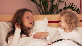 Menina bonito loving da filha e seus beijo e tentativa da mãe dormir na cama branca video estoque