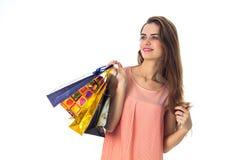 A menina bonito mantém à disposição muitos pacotes e sorriso diferentes isolados no fundo branco Imagem de Stock Royalty Free