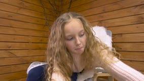 Menina bonito na cadeira que toma um presente vídeos de arquivo
