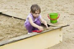 Menina bonito na caixa de areia Fotografia de Stock