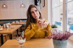 Menina bonito na camiseta amarela na moda que pensa sobre algo ao descansar no café com vidro do cappuccino indoor fotografia de stock
