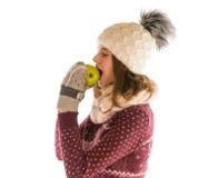 Menina bonito na camiseta, no chapéu, no lenço e em mitenes mornos comendo um appl Fotos de Stock Royalty Free