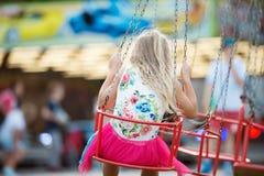 Menina bonito na feira de divertimento, passeio chain do balanço Imagens de Stock Royalty Free