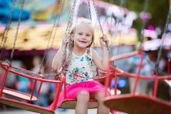 Menina bonito na feira de divertimento, passeio chain do balanço Foto de Stock Royalty Free