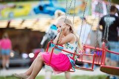 Menina bonito na feira de divertimento, passeio chain do balanço Fotografia de Stock Royalty Free