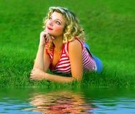 Menina bonito na grama verde perto do rivershore foto de stock