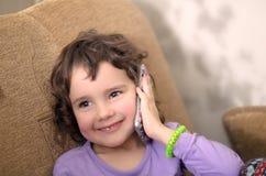 A menina bonito na roupa ocasional está falando no phon móvel Imagens de Stock