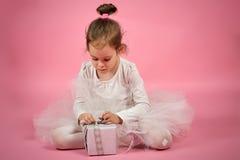 A menina bonito na saia do tule abre um presente em um fundo cor-de-rosa fotografia de stock royalty free