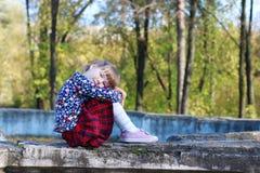 A menina bonito na saia vermelha senta-se na fonte velha imagens de stock royalty free