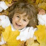Menina bonito nas folhas de outono Fotos de Stock