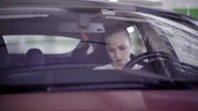 A menina bonito nervosa vestida na camisa branca senta-se no carro vermelho atrás do volante vídeos de arquivo