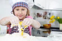 Menina bonito no avental que cozinha biscoitos Fotografia de Stock