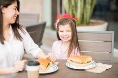 Menina bonito no café com sua mãe foto de stock royalty free