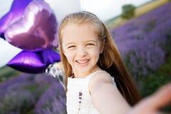 Menina bonito no campo da alfazema que guarda o ramalhete de flores roxas fotografia de stock royalty free