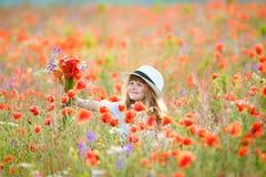 Menina bonito no campo da papoila com flores fotografia de stock royalty free