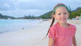 Menina bonito no chapéu na praia durante férias das caraíbas filme