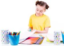 A menina bonito no corte amarelo do t-shirt scissor o cartão Imagem de Stock