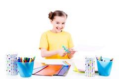 A menina bonito no corte amarelo do t-shirt scissor o cartão Fotografia de Stock Royalty Free