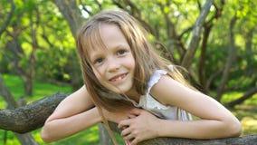 A menina bonito no jardim de florescência da árvore de maçã aprecia o dia morno vídeos de arquivo