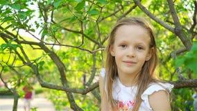 A menina bonito no jardim de florescência da árvore de maçã aprecia o dia morno video estoque