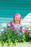Menina bonito no jardim em um fundo da cerca de turquesa Fotografia de Stock