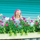Menina bonito no jardim no fundo da cerca de turquesa Imagens de Stock Royalty Free