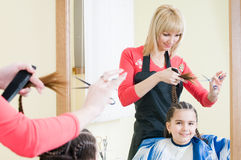 Menina bonito no salão de beleza do cabeleireiro Foto de Stock