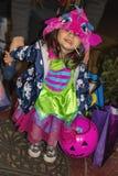 A menina bonito no traje colorido de Dia das Bruxas e o otário em suas esperas da boca no patamar para o truque r tratam doces imagem de stock