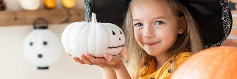 Menina bonito no traje da bruxa que guarda a abóbora pintado à mão e o sorriso Conceito de Halloween imagens de stock