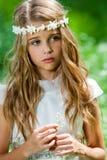 Menina bonito no vestido branco que guarda a flor. Foto de Stock