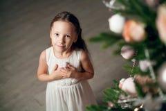 Menina bonito no vestido perto da árvore de Natal imagem de stock